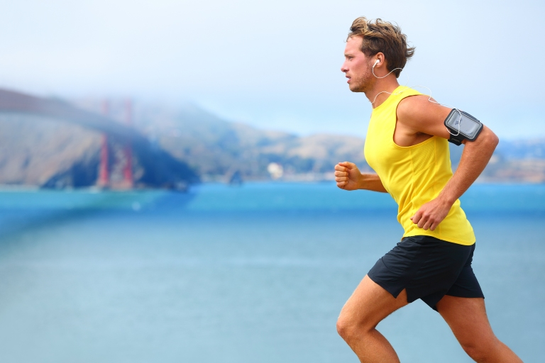 Athlete running man - male runner in San Francisco listening to
